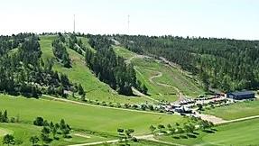Laskettelukeskus ilmasta kuvattuna kesäasussaan, vihreät rinteet ja metsät