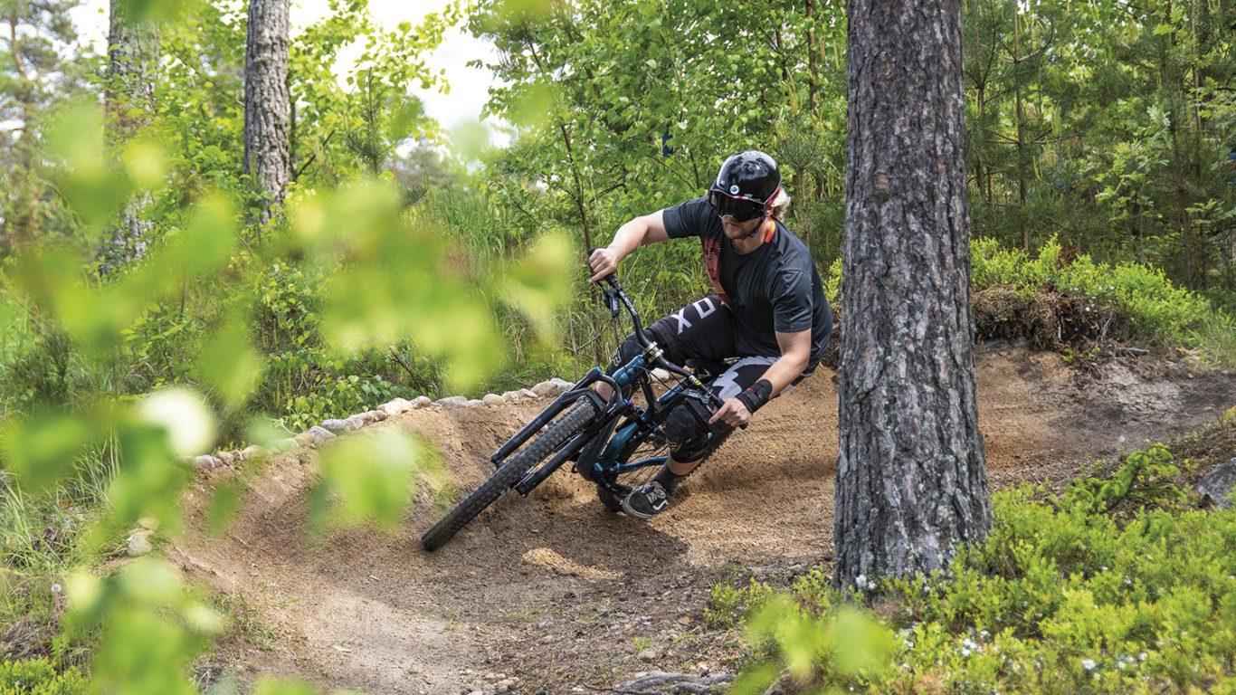 mies ajaa maastopyörällä mutkassa rinnettä alas puuta kiertäen