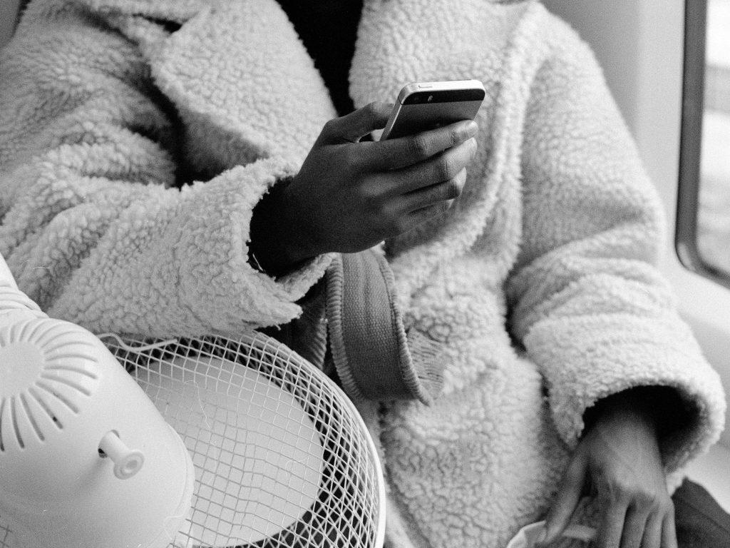Mustavalkoinen valokuva. Henkilö istuu aamutakissa ja pitää kädessään alypuhelinta.