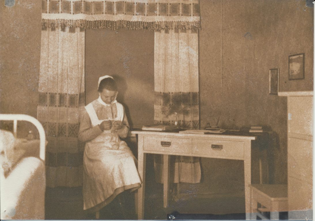Mustavalkoinen valokuva sairaanhoitajasta tekemässä työtään.