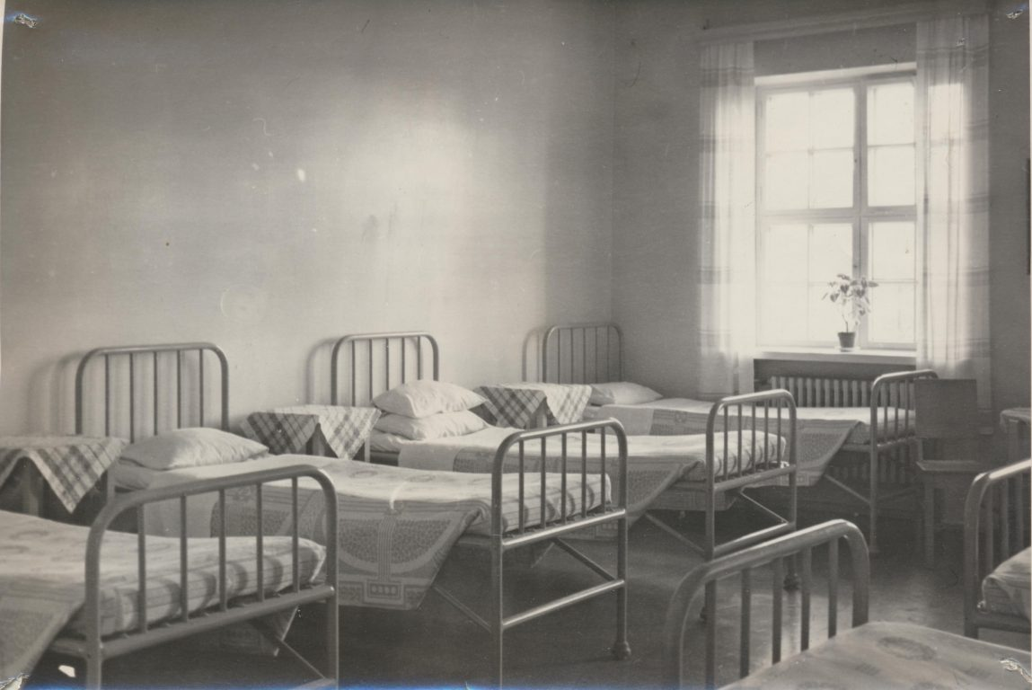 Mustavalkoinen valokuva vanhasta sairaalan makuusalista. rautasänkyjä.