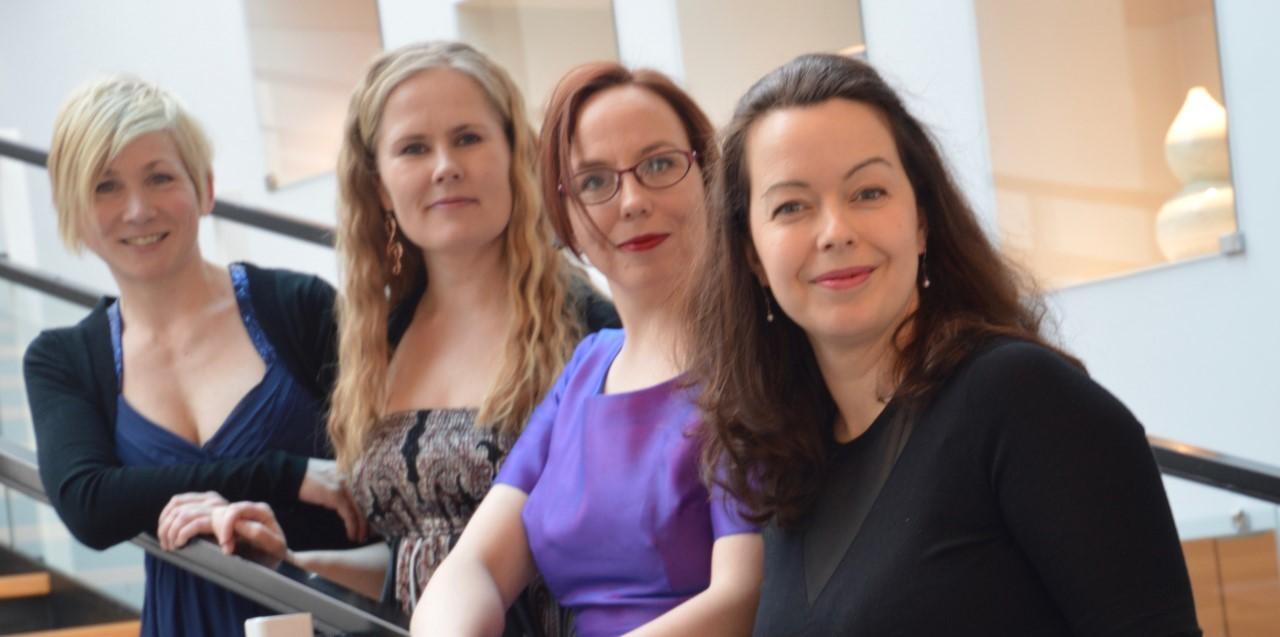 neljä naista värikkäissä vaatteissa portaikossa