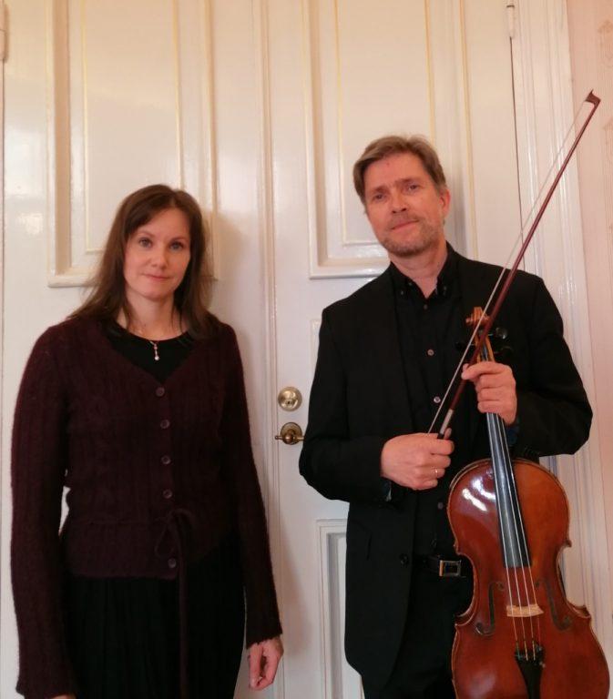 oven edessä Angela Saarinen ja Antti Vesterinen, viulu kädessä