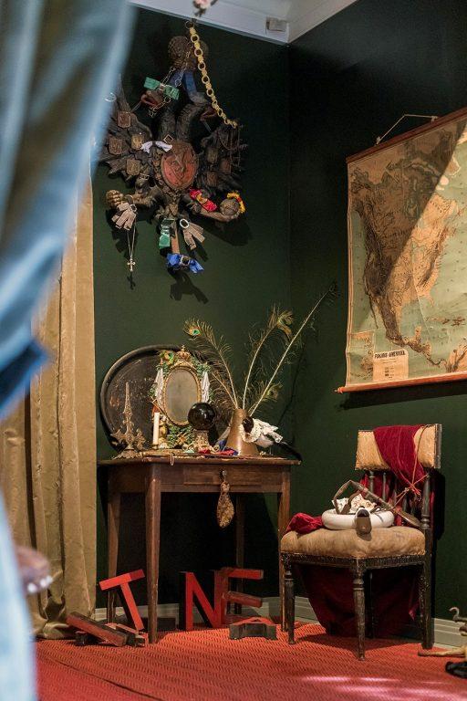 Useita vanhoja pieniä esineitä, mitaleja, karttoja, huonekaluja.