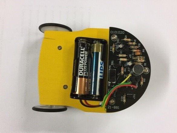 Pieni keltainen robottiauto, jossa näkyy paristo ja johtoja