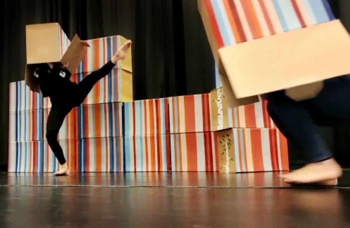 Toivomuspuu-lastenesityksen tanssijoita ja jättimäinen pahvilaatikkopalapeli.